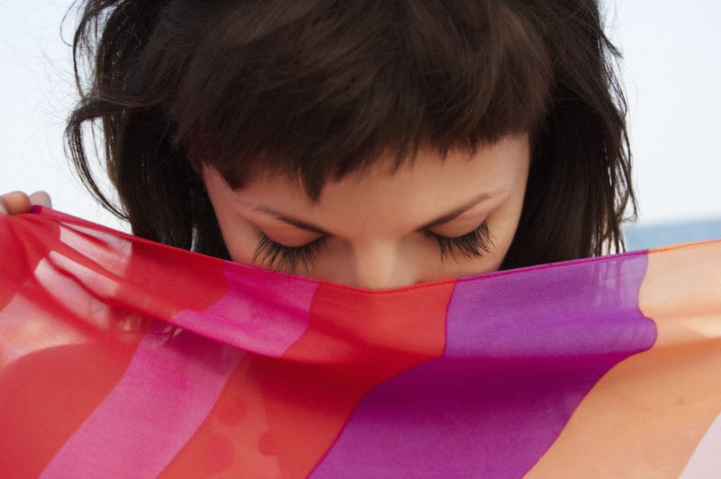 a portrait of beautiful woman with long eyelashes and with striped transparent tissue