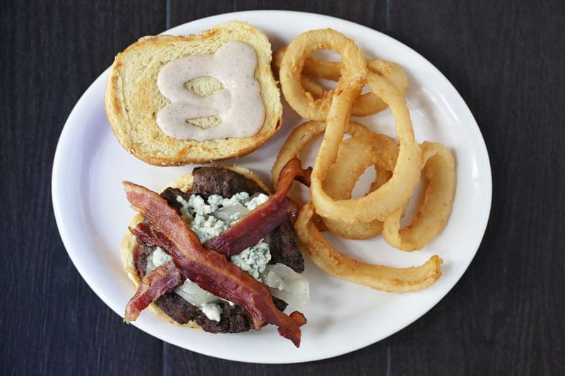 The Bucket Shop Café on Lenox Road does right by burgers. Behold the blackened beef patty with bacon and blue cheese—and side of onion rings.