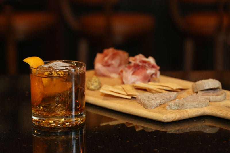 The Governor—a debonair concoction of Four Roses bourbon with hints of walnut and orange—sits well with Bourbon Bar's stellar charcuterie board.
