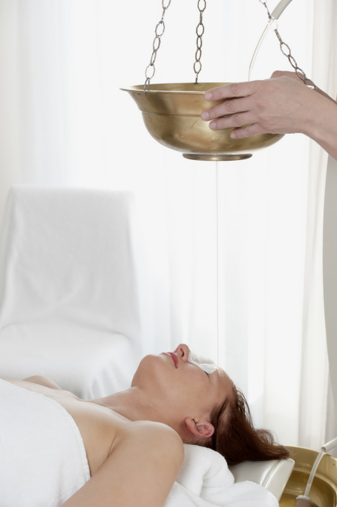 An Ayurvedic Shirodhara treatment using warm oil.