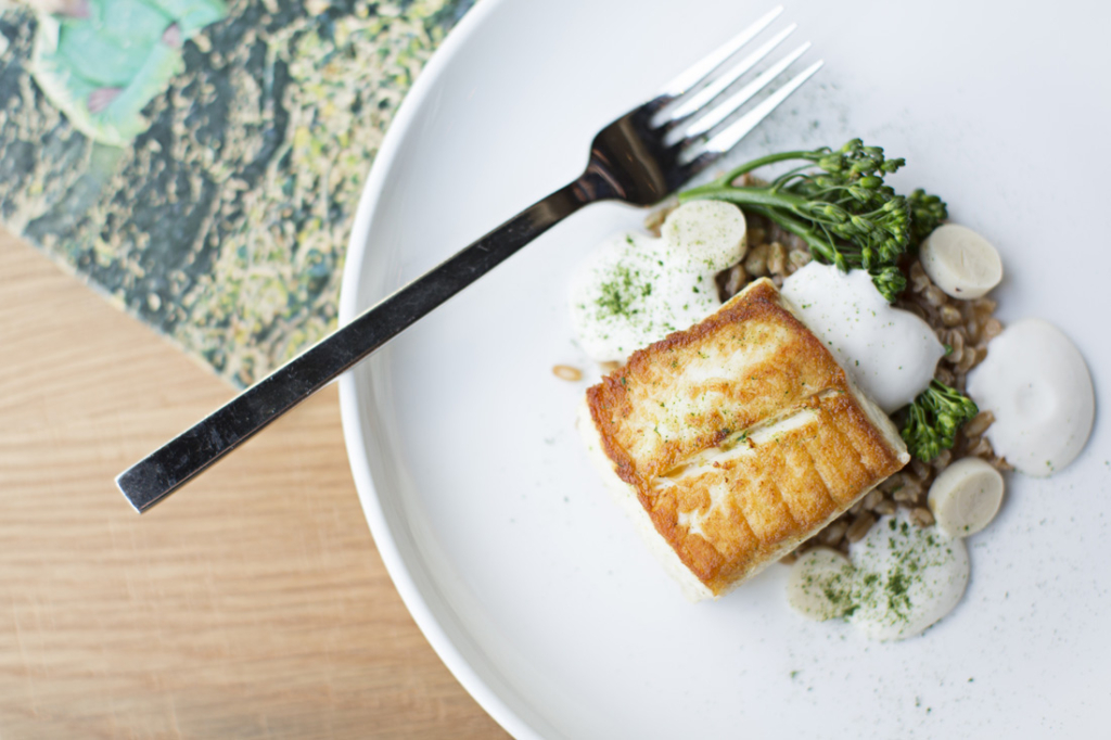 Double Zero's halibut is served with farro, broccolini, parsley, hearts of palm and beef fat foam.