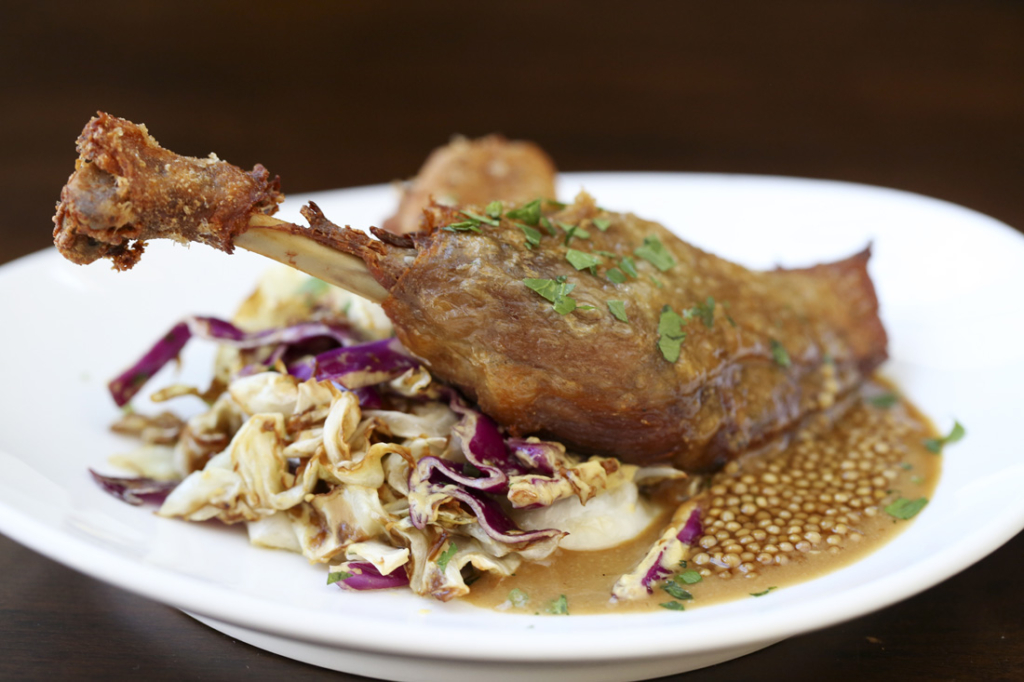 Crispy skin of duck confit with tangy mustard jus and Southern fried cabbage.