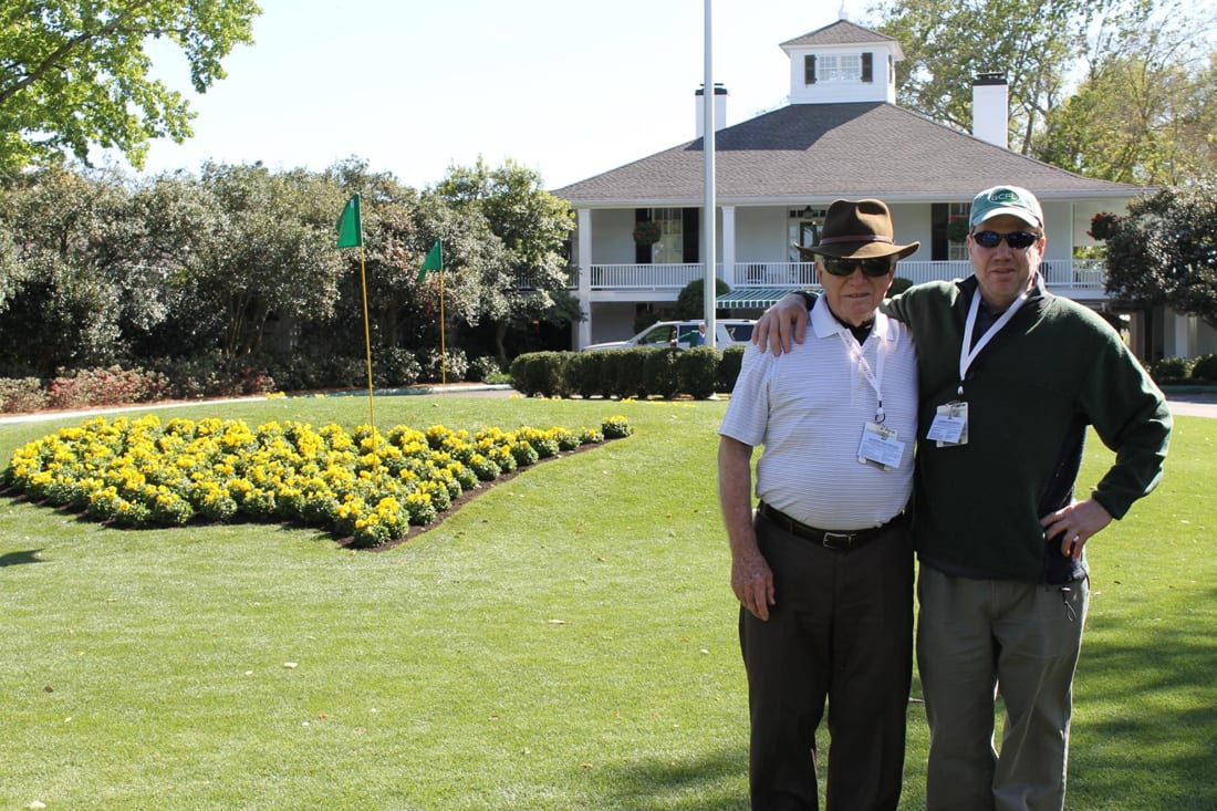 The writer and his dad posing in front of the clubhouse at the famed Augusta National golf course.