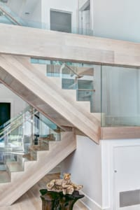 The original staircase was replaced with this chic glass and hardwood rendition.