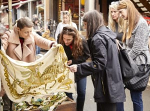 An Hermès scarf gets the once-over from Huff Harrington trip-goers.