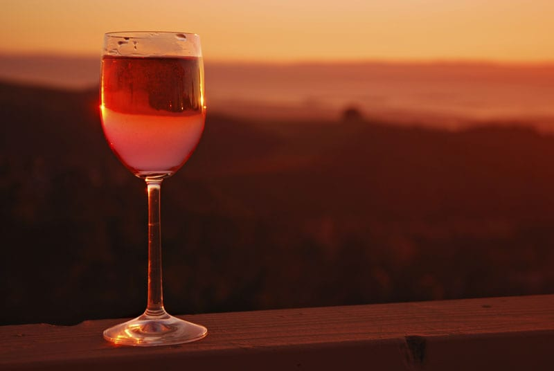 Glass of rose wine on wooden rail at sunset