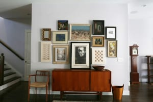 The vignette over the 1960s Danish modern dining room console from Westside Modern includes paper sculptures by Nancy Miller from Grandview Mercantile in Columbus, Ohio; a woodblock print by Leonard Baskin from a flea market; a photo by Marili Forastieri; an oil on board by Shmuel Lamm; an abstract cityscape; and an oil on wood by Hubert Shuptrine from Westside Modern.