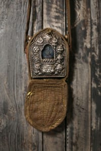 A Tibetan prayer box that Dow found at Scott Antique Markets adorns a rustic-wood wardrobe, which came with the townhouse, in the hallway outside the master bedroom.