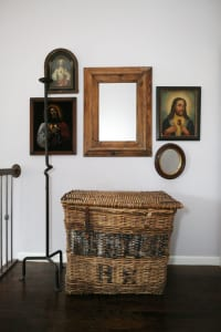 This third-floor hallway vignette features two mirrors and three framed depictions of Jesus— one velvet, one tin and a 19th century print on paper. The basket is from Europe and was used for transporting yarns.