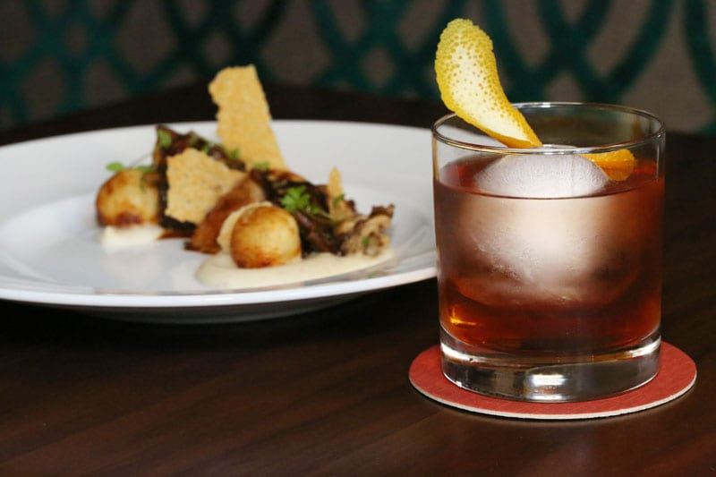 A Cocktail à la Louisiane stands ready to lift your spirits; but do take time to savor the luscious Truffle Potato Pierogi Dumplings.