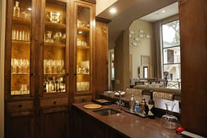 """During the home's renovation, the Bells hollowed out a corner of the great room to create a full bar where a countertop, sink and glass shelves had been. """"I love the way it turned out, and we use it all the time,"""" Jennifer says."""