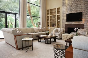 The great room, with its soaring ceiling and windows, is a comfortable space where the family gathers for everything from meals to televised football games. The sectionals and square, brass-top tables that stand in the center are David Herchik's design.