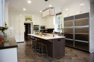 """In the spacious kitchen, the couple swapped an existing island and its flat-top electric stove for a larger one that now holds six gas burners. """"I like to work with six burners so I can really cook,"""" says Jennifer, an avid at-home entertainer."""