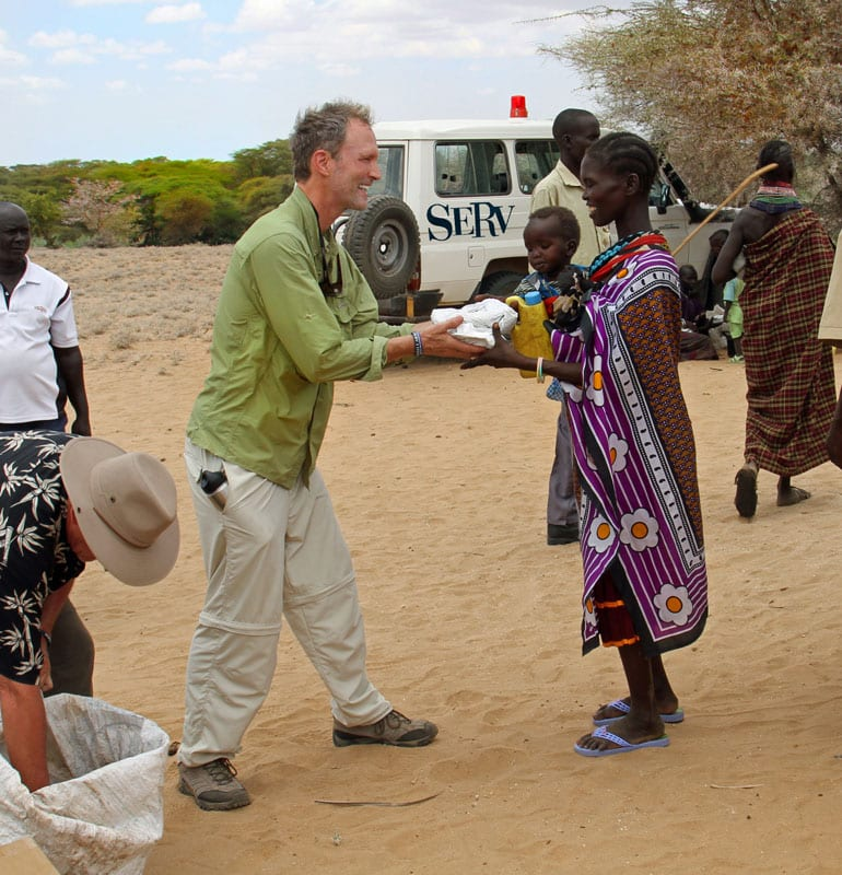 SERV volunteer Tom Sullivan hands out 10-year water purifiers to residents of Lodwar, Africa.