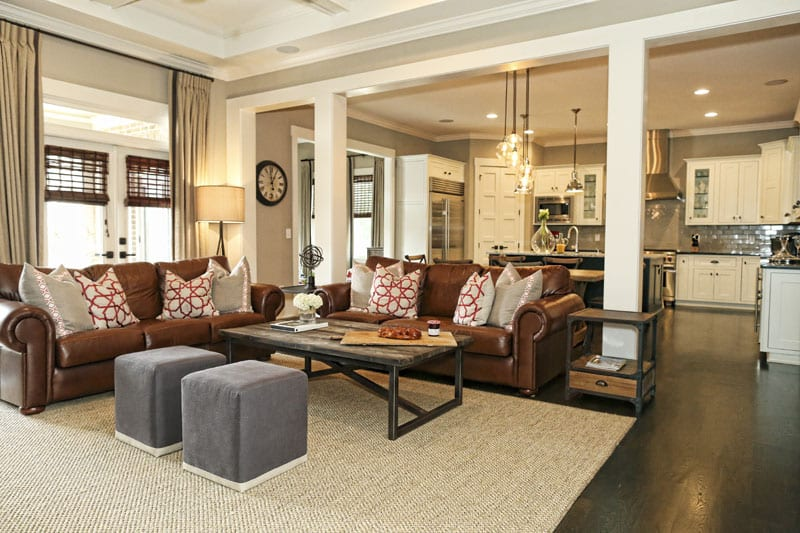 The living room, which leads to a porch with an outdoor fireplace, is comfy and casual with a coffee table from GJ Styles, a Noir floor lamp and pillows from Lacefield Designs.