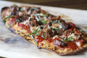 The Hogs of War flatbread is loaded with housemade chorizo, bacon and mozzarella, and moistened with arrabbiata sauce and chili oil.