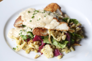 Chicken schnitzel and herbed spaetzle is comfort food with a German accent; here it's sauced with caramelized onion cream and served atop a pile of braised red cabbage and haricots verts.
