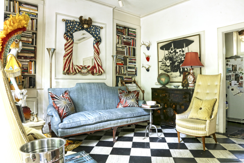 In the main living room—formerly a garage—is a star-spangled Americana mirror from Scott Antique Markets. Checkerboard floors offer graphic pop, enhanced by the Jim Thompson silk pillows atop the English mahogany sofa.