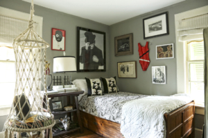"The guest room's launching point was a ""ridiculous"" pair of needlepoint nun pillows Loftin found at Scott Antique Markets. There are also vintage posters, a red bathing suit sculpture and eye-catching portrait of Elton John."