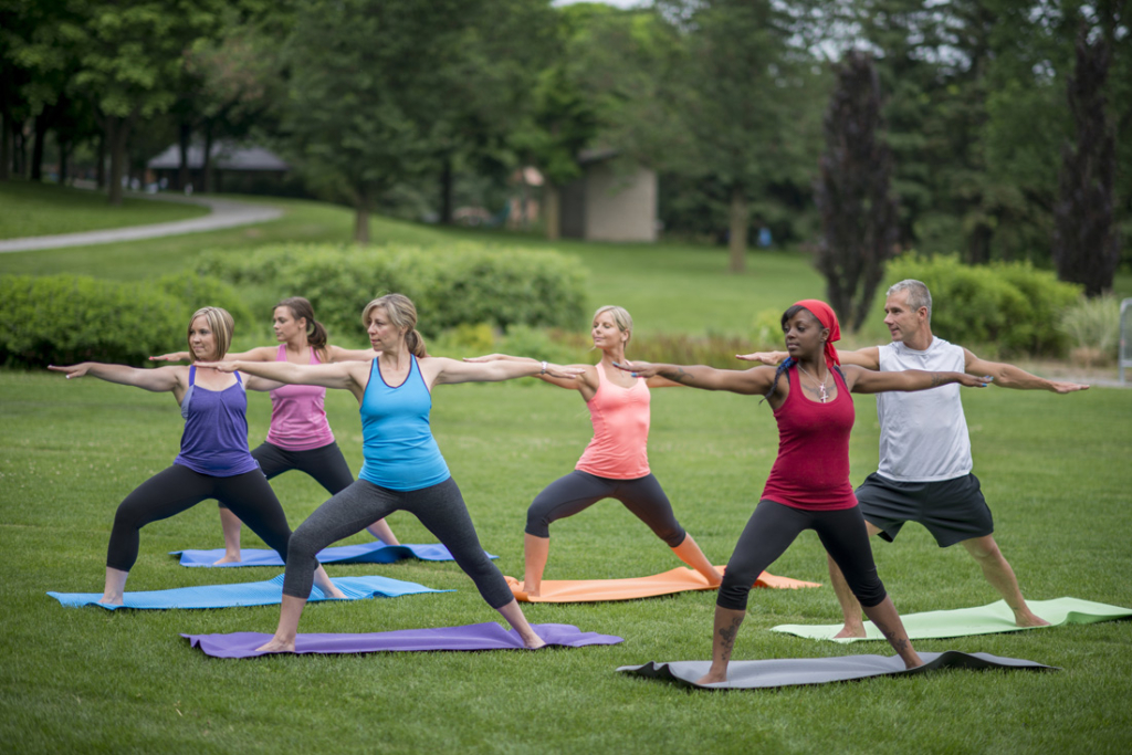 A multi-ethnic group of adults are standing in warrior two pose during their outdoor yoga class at the park.