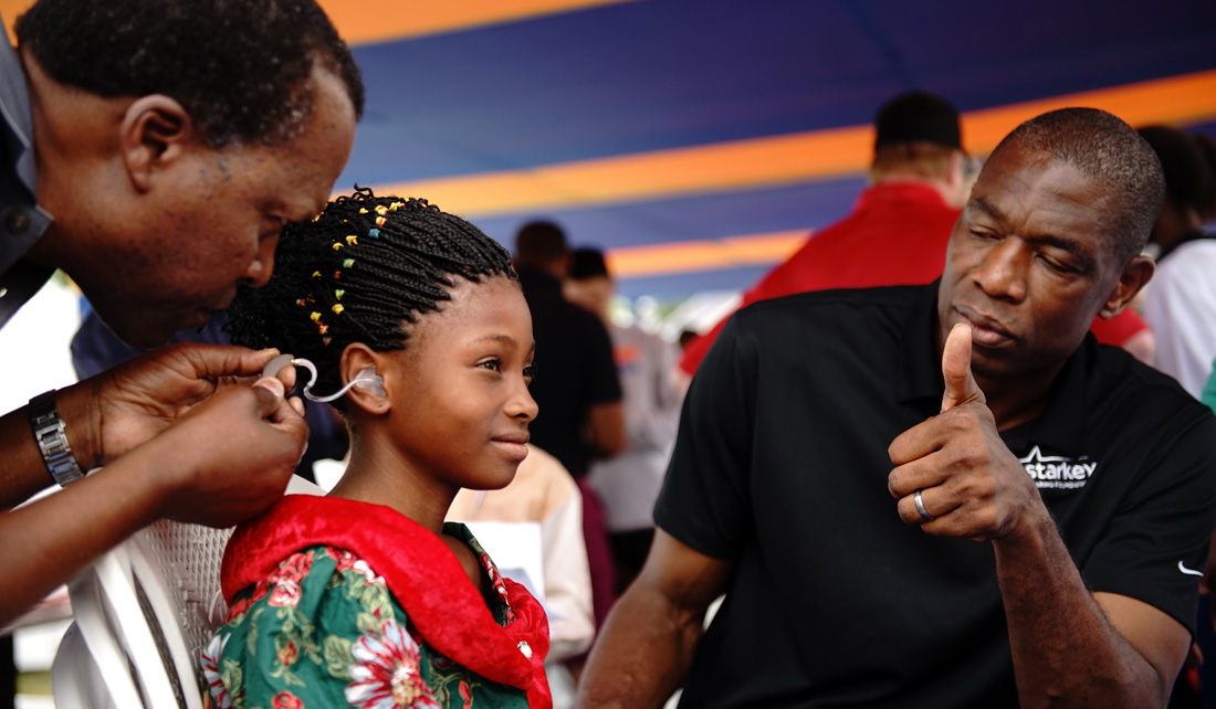 Mutombo looks on as a 9-year-old girl hears sound for the first time, thanks to a partnership between the Dikembe Mutombo Foundation and The Starkey Hearing Foundation.