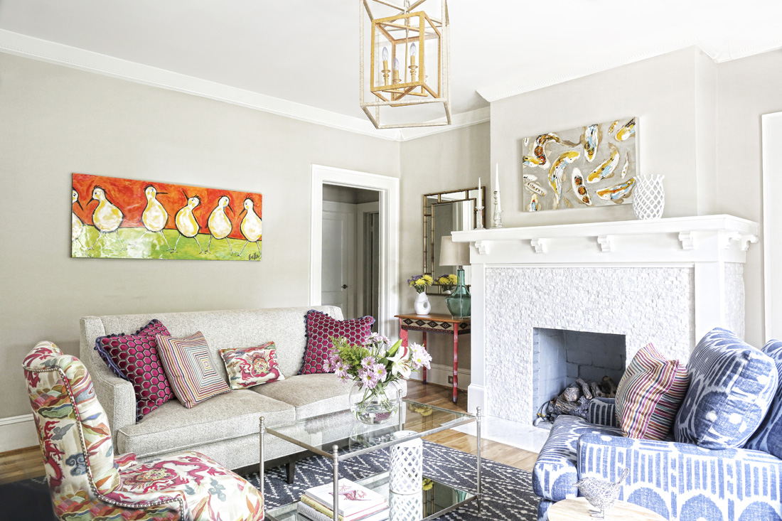 The sunlit living room is bright and cheerful, thanks to the colorful artwork and fabrics Hazel picked out with designer Rachel Oliver at ADAC.