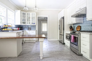 Transformed from a dated 1920s style, the nearly all-white kitchen features a custom designed wood-top peninsula that is one of Hazel and Lindquist's favorite places to hang out.