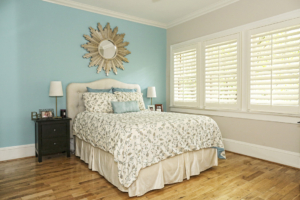 With a wall painted blue and the other lined with plantation shutters, Lindquist's room features lots of DIY, including a sunburst mirror she painted silver and the headboard and bed linens handmade by her mom.