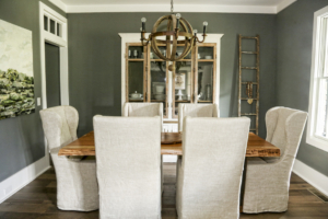 The atmospheric dining room features slipcovered-linen high-back chairs from Restoration Hardware, a felled-pecan wood dining table made by Shane's company, WoodKith, and a wine barrel-stave chandelier by BoBo Intriguing Objects.