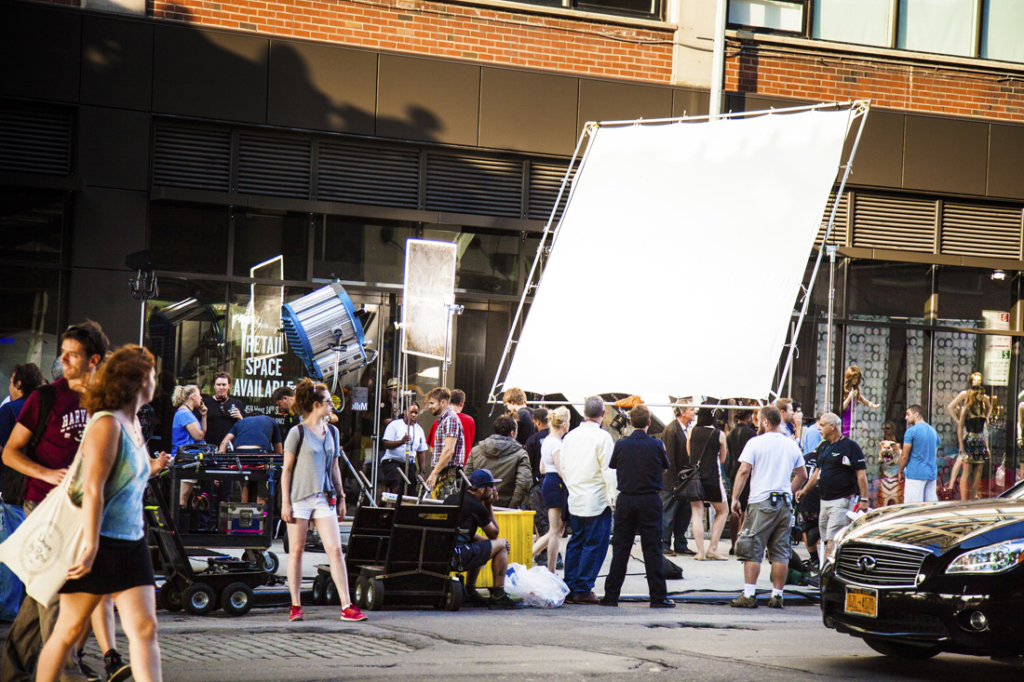 New York City, New York, United States - August 21, 2014: Cameramen and crew setting up a shoot on street in Chelsea, New York for a movie set. A lot of crowd and curious people looking at the scene.