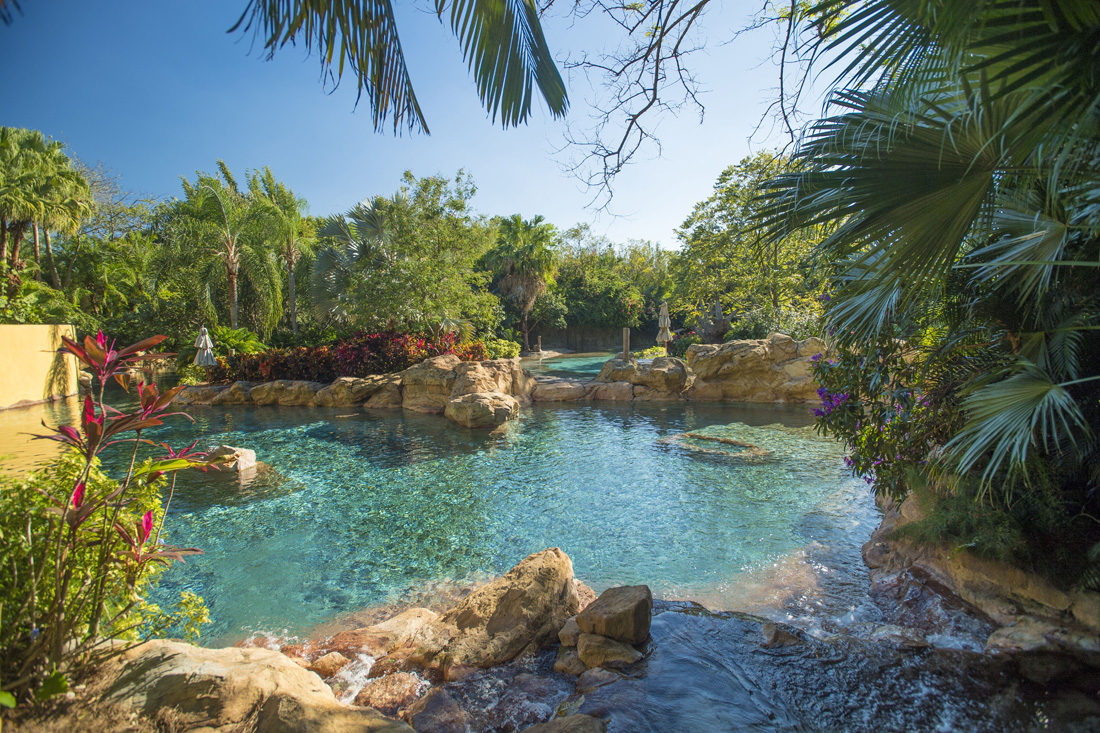 The crystal blue waters of a lazy river and lagoon invite visitors to relax and soak up the Florida sun.