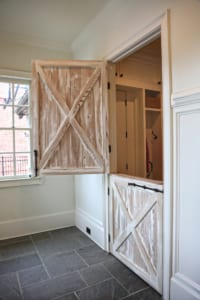A whitewashed Dutch door opens into a well-organized mudroom (once the garage).