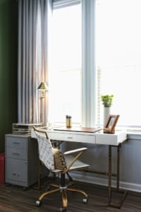 The living room's workstation follows the gold and neutrals motif and overlooks the street below.