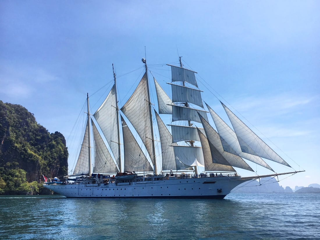 The Star Clipper floats on the Andaman Sea at full sail.