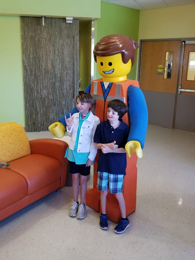 Scottish Rite patients Lexie and Malachi Delaney pose with Lego character Emmet at the hospital's new Magic Mobile Unit.