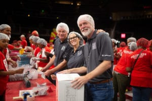 From left to right: Atlanta Hawks owners Tony Ressler and Jami Gertz and State Farm senior vice president Dan Krause were among the thousands packing food for the hungry at State Farm Arena.