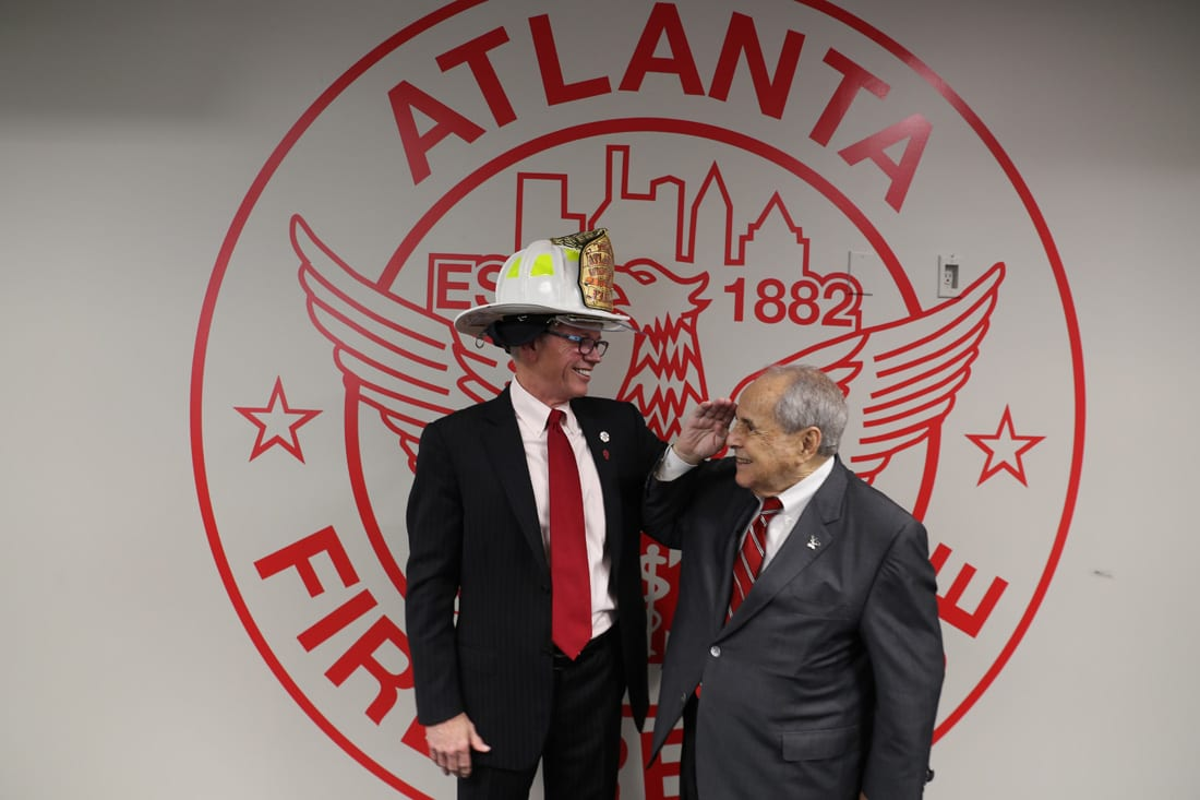 Buckhead Coalition president Sam Massell (right) salutes Atlanta Fire Rescue Foundation honoree Jacques Murphy.