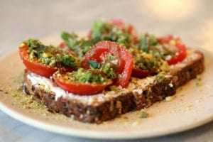 Tangy goat cheese and nutty pistachio pesto add creamy, crunchy layers to the tomato toast appetizer.