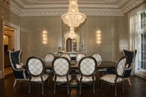The dining room is furnished with a Marge Carson table, ornate end chairs from Massoud Furniture and a chandelier from Progressive Lighting.
