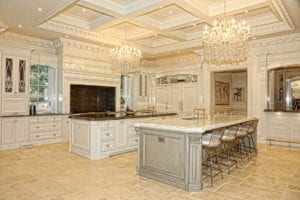The spacious kitchen boasts two islands and two chandeliers.