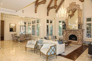 The family room features high ceilings with stained beams ideal for showcasing the antique stone fireplace.