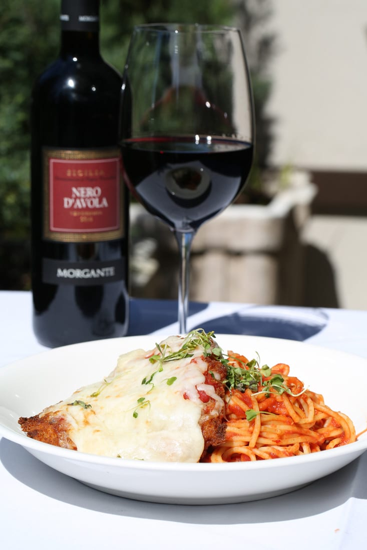 A glass of Sicilian Morgante Nero d'Avola is the perfect accompaniment to the flavorful chicken parmigiana at Cibo e Beve.